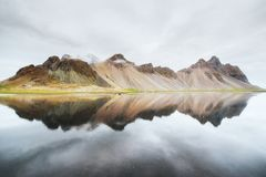 Amazing mountains reflected in the water at sunset. Stoksnes, Iceland.  Royalty Free Stock Photo