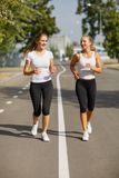 Gorgeous girls running on the blurred background. Sporty youth. Morning jogging concept. Royalty Free Stock Images