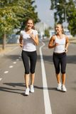Gorgeous girls running on the blurred background. Sporty youth. Morning jogging concept. Stock Photos