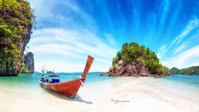 Amazing nature and exotic travel destination in Thailand. Thai tourist boat on white sand beach of small tropical island Royalty Free Stock Image
