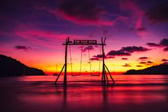 Scenic swings in the sea for a couple of lovers in love with a beautiful sunset stock photography
