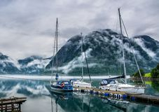 Amazing nature landscape view of lake surrounded by foggy mountains. Sailing vessels or ships. Nature lake. Forest natural. Location: Scandinavian Mountains stock image