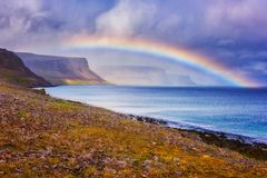 Amazing nature, scenic day time landscape with rainbow over the ocean, cliffs and dramatic cloudy sky, Atlantic shore, Iceland. Travel outdoor summer royalty free stock photo