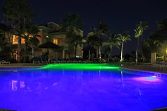 Amazing night landscape view. Blue pool water with green lights. Building with lighted windows and green plants on dark sky backgr. Ound. Aruba island nature Stock Photos