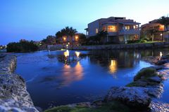 Amazing night landscape view. Running water, building with lighted windows and green plants on blue sky background. Aruba island n. Ature. Beautiful background Stock Photography