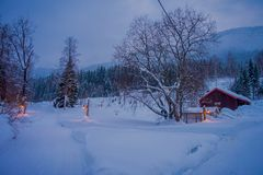 Amazing night view of traditional wooden houses with snow in the roof in stunning nature background, with some lights. And posts at outdoors in Valdres region Stock Photos