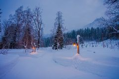 Amazing night view of traditional wooden houses with snow in the roof in stunning nature background, with some lights. And posts at outdoors in Valdres region stock images