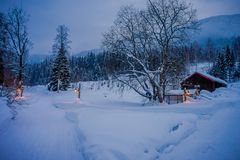 Amazing night view of traditional wooden houses with snow in the roof in stunning nature background, with some lights. And posts at outdoors in Valdres region royalty free stock image