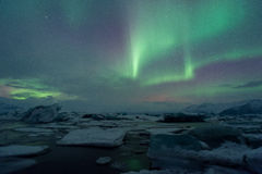 The amazing northern lights over the glacier lagoon in winter Iceland. Stock Photos