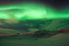 The amazing northern lights over the landscape in winter Iceland. Stock Photos
