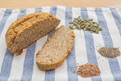 Amazing nut and seeds bread with pumpkin, flax and chia seeds on a kitchen cloth. Royalty Free Stock Photo