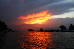 Amazing orange sunset between clouds over water. Amazing orange sunset captured over the water from Danube Delta Romania. The sky seems to be on fire Stock Photography