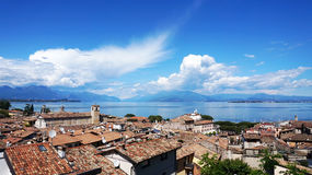Amazing panorama from Desenzano castle on Lake Garda with old city roofs, mountains, white clouds and sailboats on the lake Royalty Free Stock Image