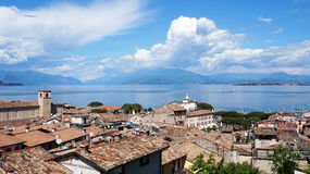 Amazing panorama from Desenzano castle on Lake Garda with old city roofs, mountains, white clouds and sailboats on the lake Royalty Free Stock Photography