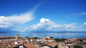 Amazing panorama from Desenzano castle on Lake Garda with old city roofs, mountains, white clouds and sailboats on the lake, Stock Photography