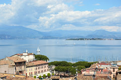 Amazing panorama from Desenzano castle on Lake Garda with old city roofs, mountains, white clouds and sailboats on the lake, Desen Royalty Free Stock Images