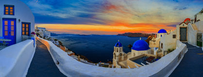 Amazing panorama sunset view with white houses in Oia village on. Santorini island in Greece Royalty Free Stock Photo