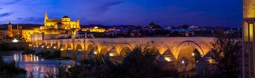 Amazing panoramic view of Roman bridge and Mezquita of Cordoba glowing in night royalty free stock images