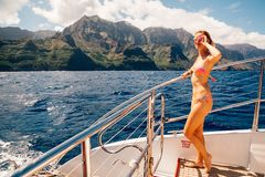 Amazing paradise view Young lady sailing. Young lady sailing on yacht down the Na Pali cliffs by Kauai island on Hawaii Stock Photos
