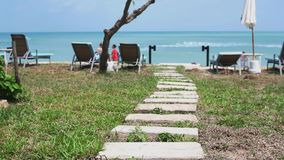 Wonderful path from stones to the ocean shore with umbrellas and sunbeds in slow motion. Thailand. 3840x2160. An Amazing path from stones to the ocean shore stock video footage