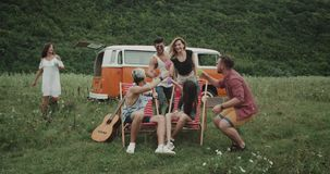 Amazing picnic, with stylish young friends , sitting on the picnic chairs , someone standing up, they holding colorful. Glasses and cheers with each other, they stock footage
