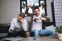 Gamers playing party. The amazing picture of winning and loosing at the same time. Two gamers has played an interesting game. The guy on the left has lost the Royalty Free Stock Image
