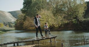 Amazing place at nature dad with his son spending a day together , catching fish and playing together. stock video