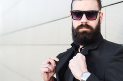 Amazing portrait of a man with a long beard and glasses in a bla Stock Image