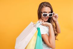 Amazing pretty young woman holding shopping bags. Royalty Free Stock Images