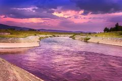 Amazing purple sunset and fluffy clouds over curvy river stock images