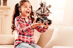 Excited preteen child getting emotional over robot toy. This is amazing. Radiant brunette girl keeping her mouth wide opened while relaxing on a sofa and looking Royalty Free Stock Photos