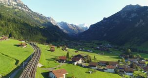 Foothills of Switzerland. Amazing railroad aerial view alpine foothill in Switzerland. Scenic peaceful view of countryside life. Top view of traditional swiss stock footage