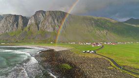 Amazing rainbow over blue ocean waves crashing on stone beach in rural mountain hill village 4k aerial drone landscape stock video footage