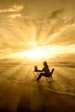 Amazing rays of light of woman study on beach. Silhouette of woman study on the beach under beautiful rays of light Stock Photos