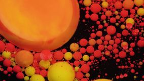 Amazing red and yellow bubbles of paint on the oil surface. Paint in oil. Slow motion stock video