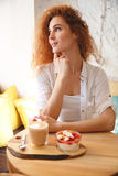 Amazing redhead young lady sitting in cafe while eating dessert. Stock Images
