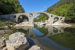 Amazing Reflection of Devil`s Bridge in Arda river and Rhodopes mountain, Bulgaria. Amazing Reflection of Devil`s Bridge in Arda river and Rhodopes mountain Royalty Free Stock Images