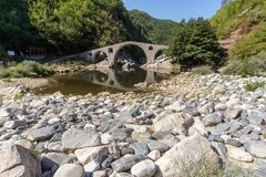 Amazing Reflection of Devil`s Bridge in Arda river and Rhodopes mountain, Bulgaria. Amazing Reflection of Devil`s Bridge in Arda river and Rhodopes mountain Royalty Free Stock Photography