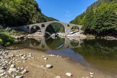 Amazing Reflection of Devil`s Bridge in Arda river and Rhodopes mountain, Bulgaria. Amazing Reflection of Devil`s Bridge in Arda river and Rhodopes mountain Stock Images