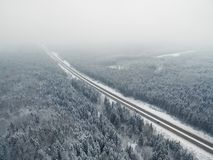 Amazing road in the frozen winter forest with driving cars. Foggy vanishing point perspective. Aerial panoramic view on the north stock image