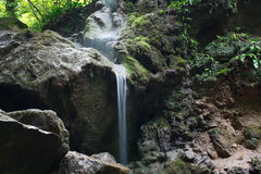 Amazing rocks covered with moss with flowing waterfall Stock Photography