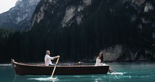 Amazing romantic couple in the middle of a lake in the wooden boat spending time together the man are rowing