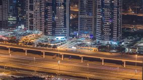 Amazing rooftop view on Sheikh Zayed road surrounded Dubai Marina and JLT skyscrapers. Dubai. Aerial view at night with traffic and metro line. United Arab stock video