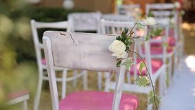 Amazing rustic decoration of wedding ceremony with hay, chairs, flower floristic compoitions and wedding dress hanging. On a tree on background stock video