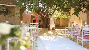 Amazing rustic decoration of wedding ceremony with hay, chairs, flower floristic compoitions and wedding dress hanging. On a tree on background stock video footage