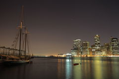 Amazing sailing ship is against Manhattan Island New York USA. Towers on Manhattan's Island at night. New York City stock photos