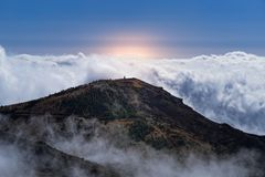 Amazing scene of mountain peak and dense clouds against sky and orange colored sunlight. View from Pico do Arieiro on Portuguese island of Madeira royalty free stock images