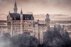 Amazing scene of mystique enchanted Neuschwanstein Castle lost in the fog. The Romanesque Revival palace built for King Ludwig II on a rugged cliff near Fussen Royalty Free Stock Photo