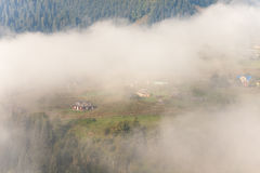 Amazing scenery of idyllic countryside with rolling hills veiled in morning fog. Aerial view of a hilltop farmhouse on a Stock Images