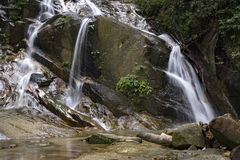 Amazing scenery of tropical waterfall flowing through the beautiful green forest. Background stock photography